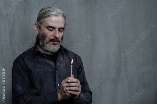 Senior man hands hold a candleon dark background. Space for text