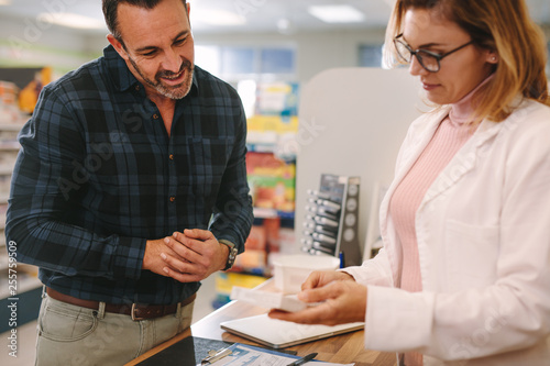 Pharmacist giving advice over a medicine to customer