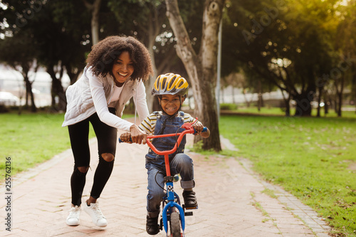 Leinwanddruck Bild Mother teaching son to ride bicycle