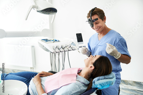 Leinwanddruck Bild Charming young lady looking at dentist and smiling