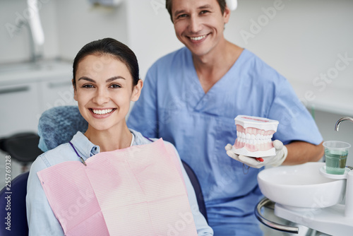 Leinwanddruck Bild Charming young lady and dentist posing at dental office