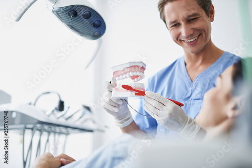 Leinwanddruck Bild Cheerful dentist showing how to brush teeth properly to young woman