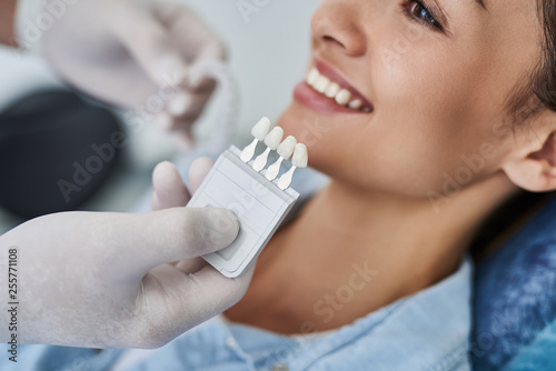 Dentist choosing color of teeth for young woman