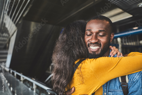 Delighted afro American man embracing with his loving girlfriend