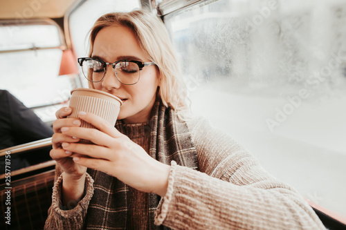 Young female drinking coffee in bus cafe