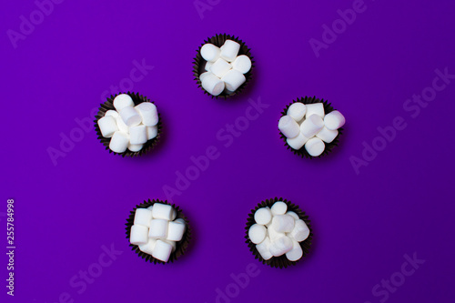 marshmallows in the forms for cakes on a purple background, five pieces. Arranged in a circle. View from above. - 255784998
