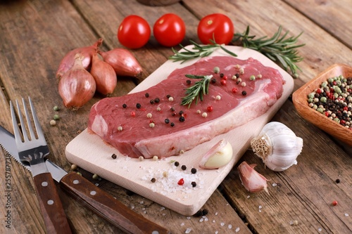 Meat - raw rumpsteak - rumpsteak  with rosemary, pepper, tomatos and spices on a rustic wooden table - 255787738