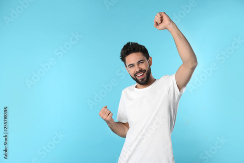Leinwanddruck Bild Portrait of happy young man on color background. Space for text