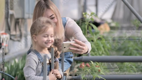 A woman with a small daughter make a selfie in a greenhouse with flowers.