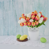 Fototapeta Tulipany - Easter background. Decorative Easter eggs and red tulips in vase. Copy space © Laima