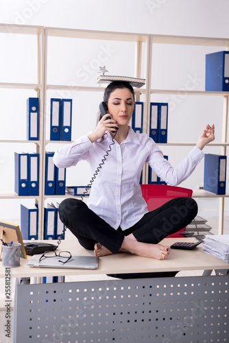 Young female employee doing exercises in the office