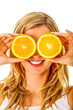 Blond woman is covering eyes by two half of orange fruit, on white background.