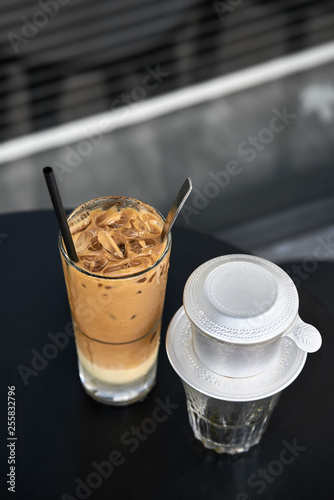 Colorful iced coffee drink on black table outdoors
