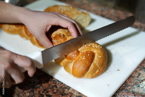 close up on person hand cutting bread by knife