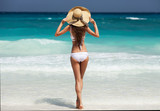 Beautiful slim woman in white bikini and hat. Enjoy tropical sunbathing.