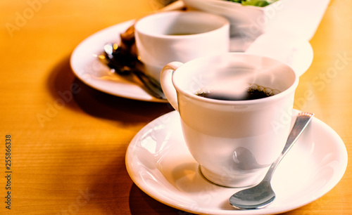 Hot coffee in white mug on wooden table in coffee shop in the morning