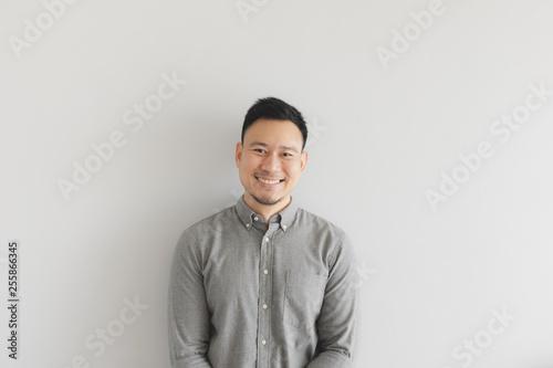 Leinwandbild Motiv Smile happy face of ordinary man in grey shirt. Concept of charming and positive thinking.