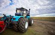 Leinwanddruck Bild - Tractor working in a field against a cloudy sky