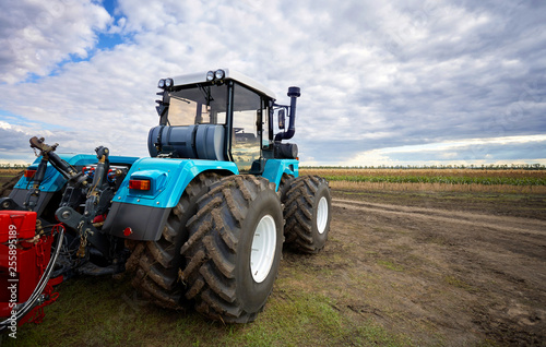 Tractor working in a field against a cloudy sky