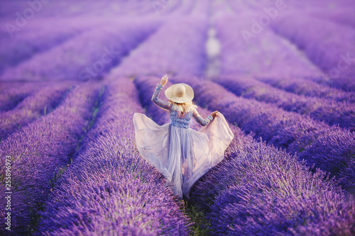Woman in lavender flowers field at sunset in purple dress. France, Provence - 255896973