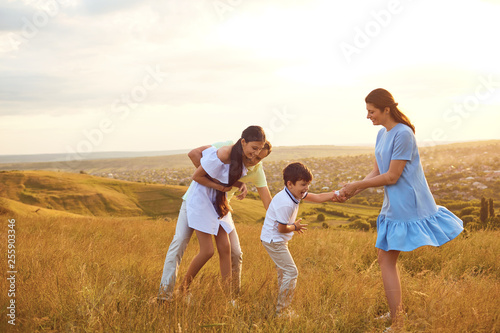 Happy family playing fun on the field at sunset.