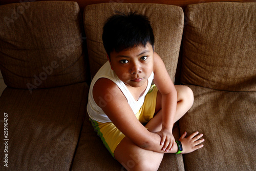 Young Asian boy sitting on a couch