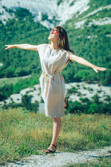 An attractive girl in sunglasses on a walk in a mountainous area enjoys a Sunny day and a good mood, standing on one leg like a ballerina with her arms spread in the form of wings. © indigo_nifght