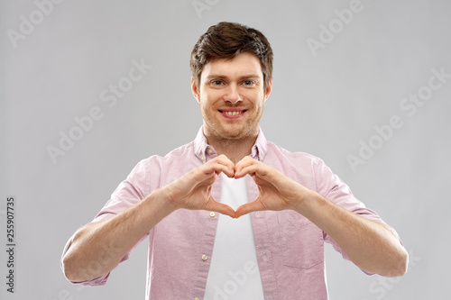 Leinwanddruck Bild love, charity and valentine's day concept - smiling man making hand heart gesture over grey background