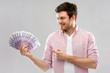 Leinwanddruck Bild - money, finance, business and people concept - smiling young man showing fan of five hundred euro bank notes over grey background