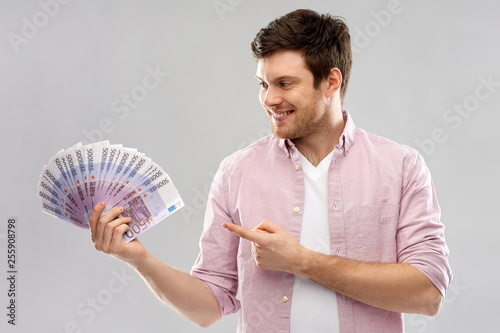 Leinwanddruck Bild money, finance, business and people concept - smiling young man showing fan of five hundred euro bank notes over grey background