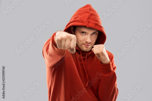 combat, aggression and people concept - young man in red hoodie fighting with fists or boxing over grey background