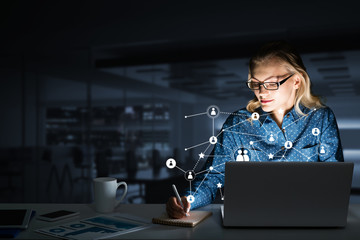 Attractive blonde wearing glasses in dark office using laptop. Mixed media