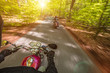 Leinwanddruck Bild - Motorcycle driver riding in spring forest, handlebars view.