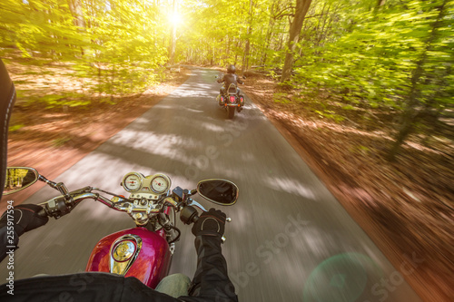 Leinwanddruck Bild Motorcycle driver riding in spring forest, handlebars view.