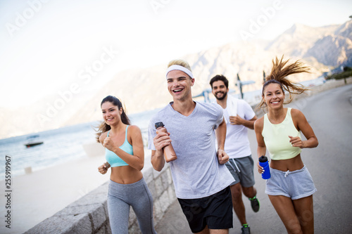 Leinwanddruck Bild Group of young people jogging and running outdoors in nature