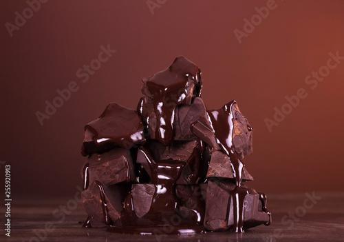 Leinwanddruck Bild Pieces of flavored chocolate molten glaze on dark background