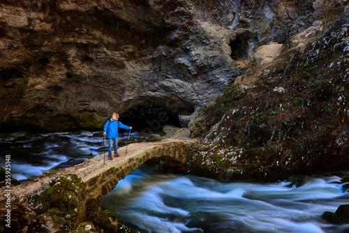 trekker on the bridge in karst cave