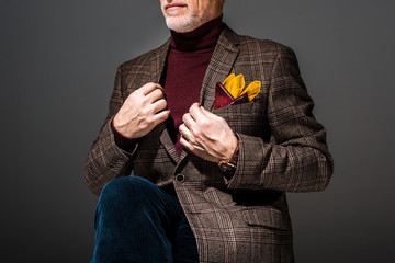cropped view of fashionable mature man on grey