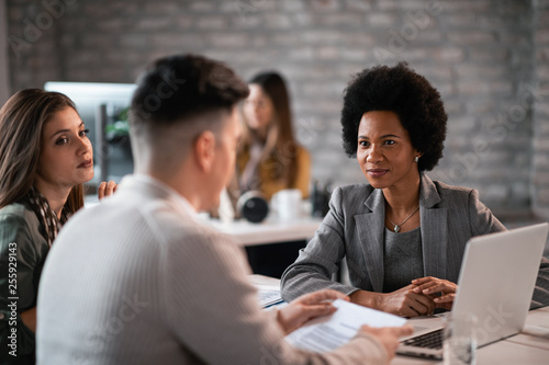 Smiling black insurance agent having a meeting with a couple in the office.