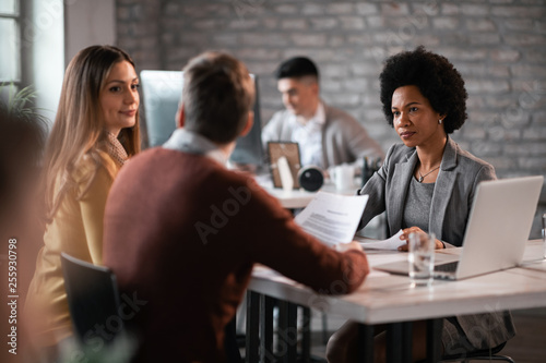 African American insurance agent having a meeting with a couple in the office.