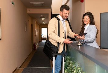 Young business man check-in in hotel, smiling female receptionist behind the hotel counter showing him available rooms on tablet.