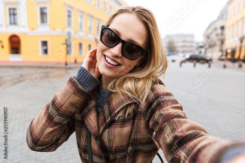 Leinwanddruck Bild Beautiful young blonde woman wearing a coat