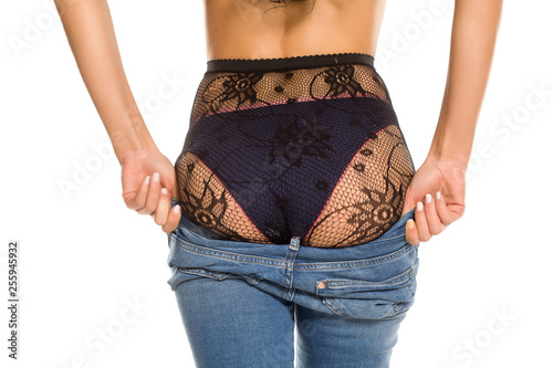 A woman putting on her tight jeans on white background - 255945932