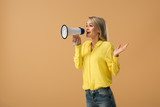 Smiling blonde woman in yellow shirt screaming in megaphone isolated on beige - 255953737