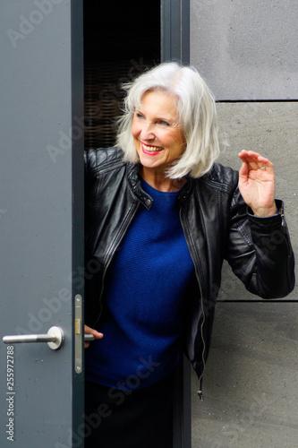 Ältere Frau mit grauen Haaren und Lederjacke