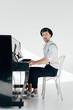 Leinwanddruck Bild - inspired pianist in white shirt and black hat playing piano