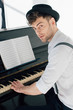 Leinwanddruck Bild - handsome pianist in stylish clothing playing piano at home