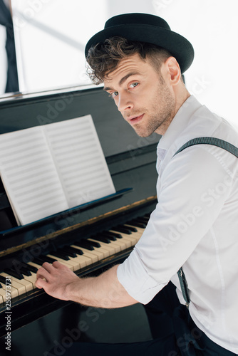 Leinwanddruck Bild handsome pianist in stylish clothing playing piano at home