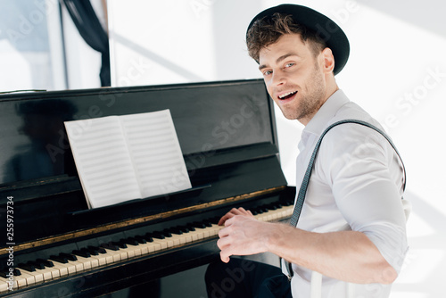 Leinwanddruck Bild smiling pianist sitting by piano and looking at camera