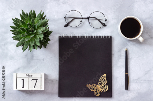 Office or home table desk. Wooden cubes calendar May 17. Black notepad, cup of coffee, succulent, glasses on marble background Concept stylish workplace Flat lay Top view